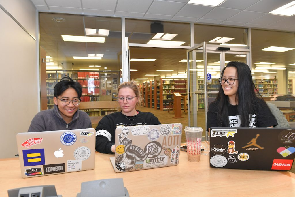 three students with laptops smiling